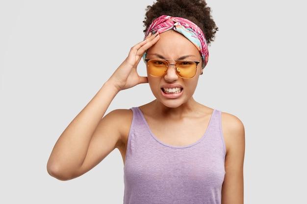 La mujer afroamericana joven desesperada frunce el ceño con insatisfacción, aprieta los dientes, mantiene la mano en la cabeza, tiene dolor de cabeza, posa contra la pared blanca. mujer atractiva de piel oscura irritada Foto gratis