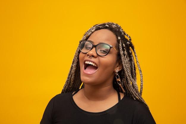 Mujer afroamericana joven hermosa con el pelo y las lentes del pavor en amarillo Foto Premium