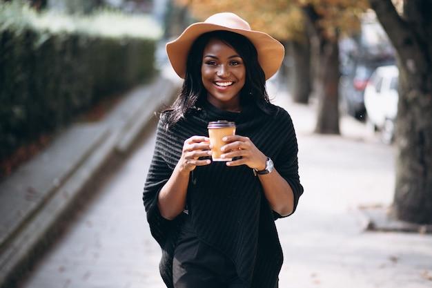 Mujer afroamericana tomando café y hablando por teléfono Foto gratis