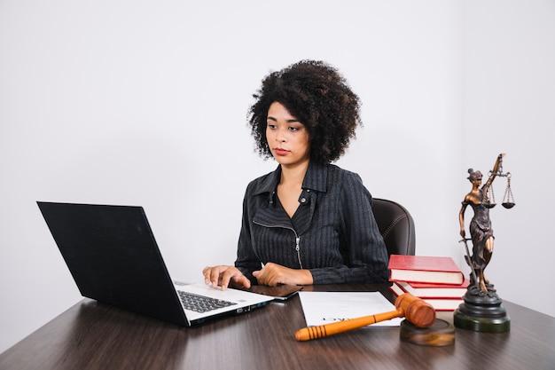 Mujer afroamericana usando una computadora portátil en la mesa cerca de un teléfono inteligente, libros, documentos y una estatua Foto gratis