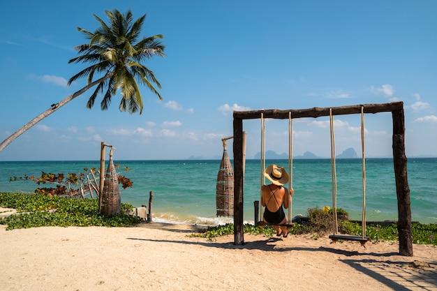 Mujer aislada en su escapada romántica de luna de miel en una playa paradisíaca con palmeras. caro resort de lujo para parejas casadas y solteros. relájate en un columpio. viaje al concepto de tailandia. Foto Premium