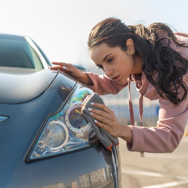 Mujer al aire libre limpiando el auto Foto gratis