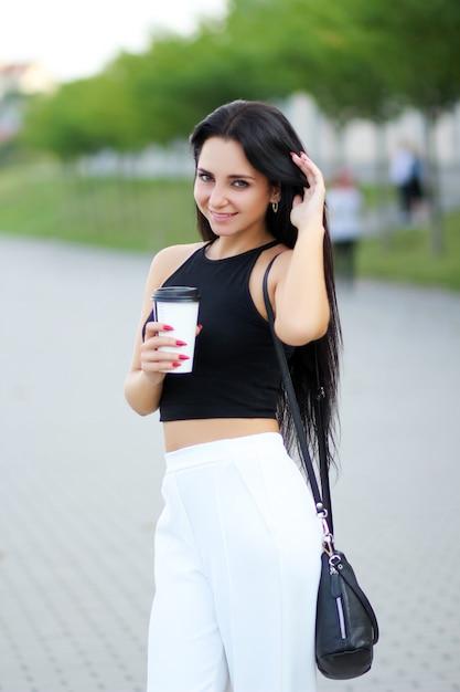 Mujer alegre en la calle bebiendo café de la mañana en el sol Foto Premium