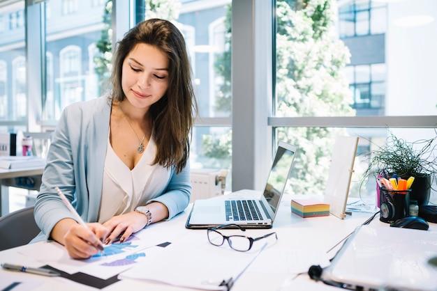 Mujer alegre escribiendo en documentos Foto Premium