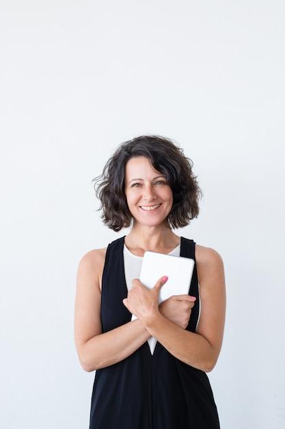 Mujer alegre feliz con tableta sonriendo a la cámara Foto gratis