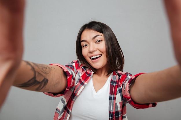 Mujer alegre hacer selfie sobre pared gris. Foto gratis