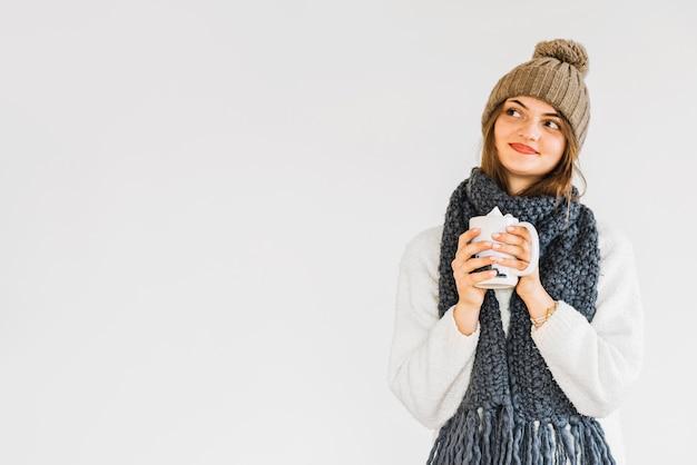 Mujer alegre joven en sombrero y bufanda con la taza de bebida Foto gratis