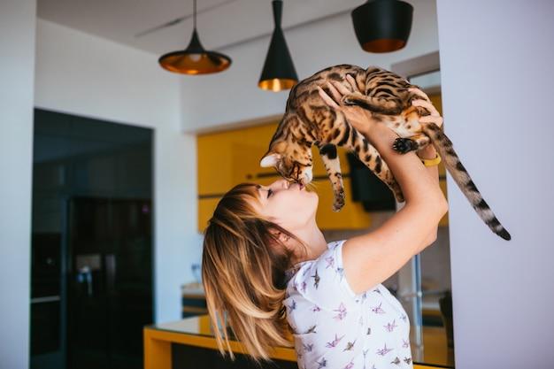 Mujer alegre levanta gato de bengala de pie en la cocina Foto gratis