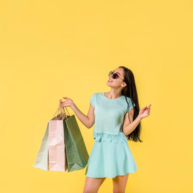 Mujer alegre de pie con bolsas de la compra. Foto gratis