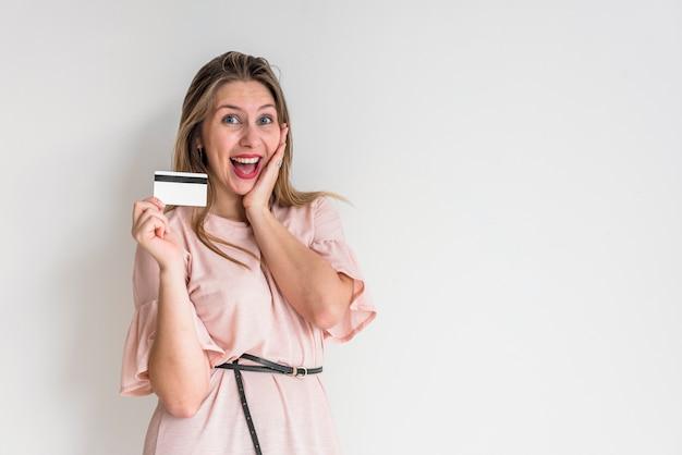 Mujer alegre de pie con tarjeta de crédito Foto gratis