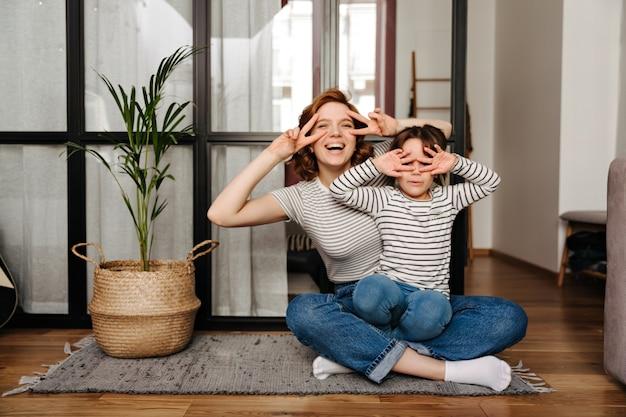 Mujer alegre y su hija divirtiéndose en la sala de estar y mostrando signos de paz. Foto gratis