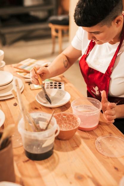 Mujer alfarero pintando vajilla de cerámica con pincel en taller Foto gratis