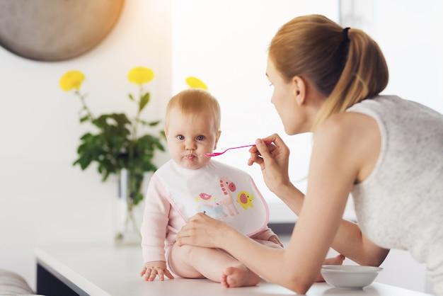 Una mujer está alimentando a un bebé con una cuchara. Foto Premium