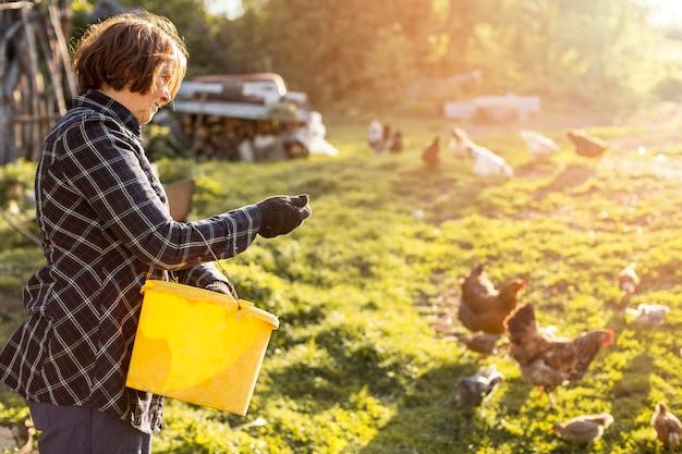 Mujer alimentando a las gallinas Foto Premium