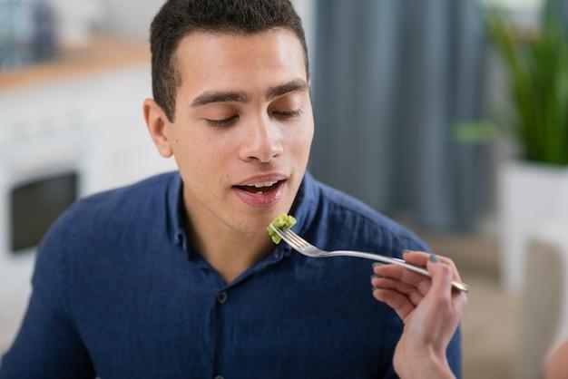 Mujer alimentando a su novio en una cena romántica Foto gratis