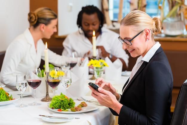 Mujer en el almuerzo de negocios que controla correos en el teléfono Foto Premium