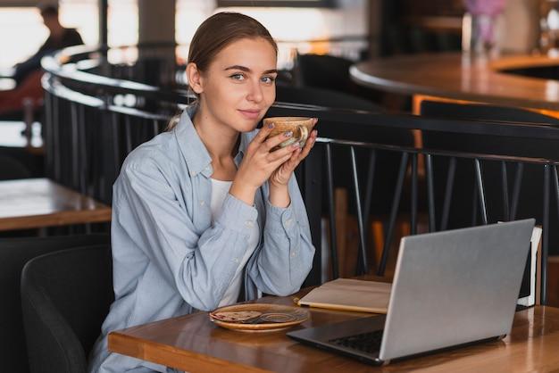 Mujer de alto ángulo en el restaurante tomando café Foto gratis