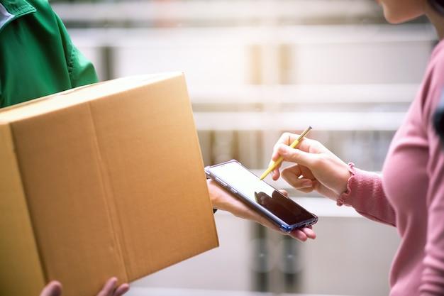 Mujer ama de casa firma un paquete de un remitente en un teléfono inteligente en la era digital, respondiendo al mundo de la tecnología sin fronteras. Foto Premium