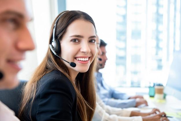 Mujer amistosa sonriente que trabaja en la oficina del centro de atención telefónica con el equipo Foto Premium