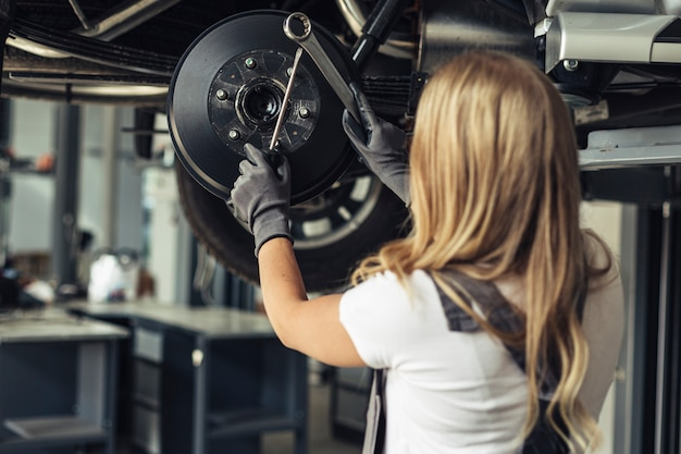 Mujer de ángulo bajo reemplazando las ruedas del automóvil Foto gratis