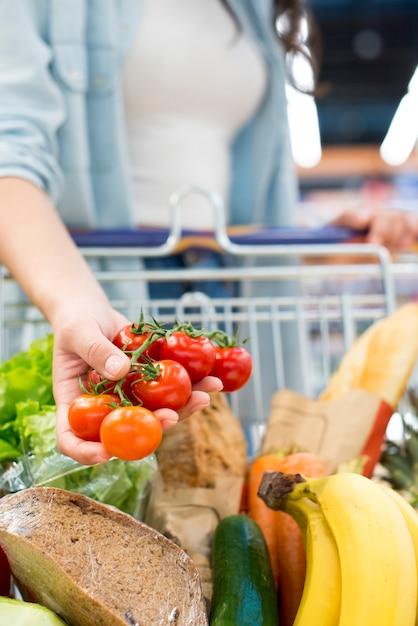 Mujer anónima que sostiene los tomates que se colocan con el carro de la compra en el supermercado Foto gratis