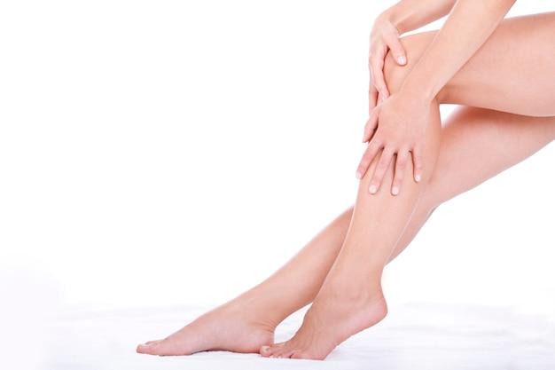 Mujer aplicando crema hidratante en las piernas Foto gratis