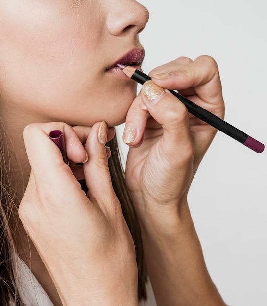 Mujer aplicando delineador de labios en modelo Foto gratis