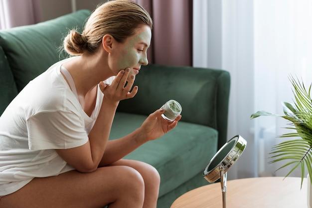 Mujer aplicando máscara facial en el espejo Foto gratis