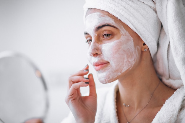 Mujer aplicando mascarilla de belleza Foto gratis