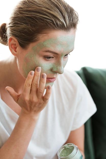 Mujer aplicando mascarilla facial orgánica Foto gratis