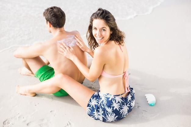 Mujer aplicando protector solar en la espalda del hombre Foto Premium