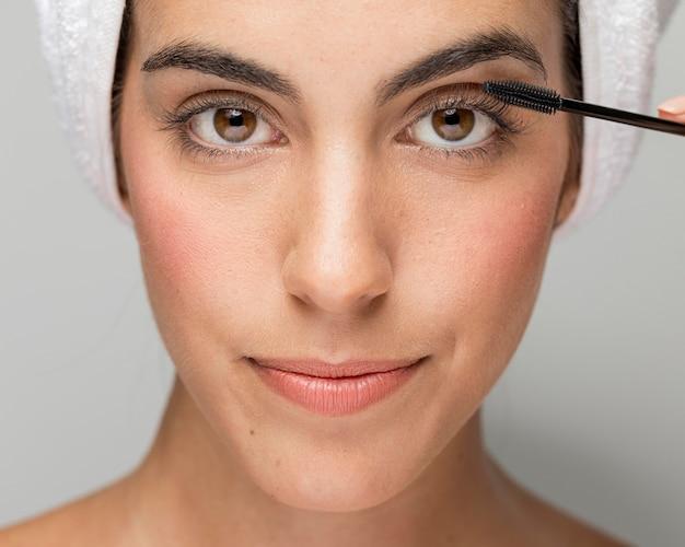 Mujer aplicando rímel en sus pestañas de cerca Foto Premium