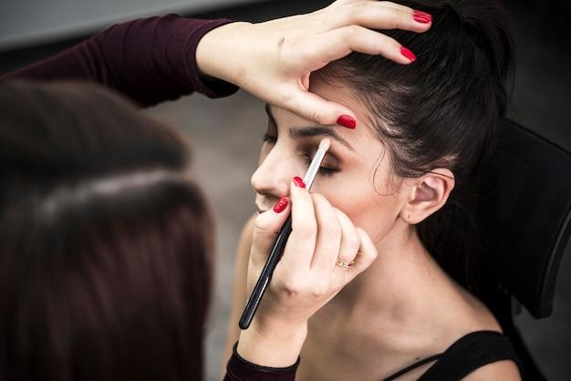 Mujer aplicando sombra de ojos en modelo Foto gratis