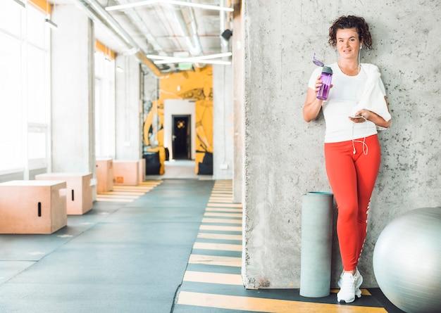 Mujer apta con la botella de agua y el teléfono móvil que se inclinan en la pared en gimnasio Foto gratis