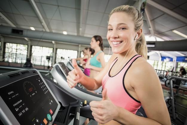 Mujer apta corriendo en la cinta mientras escucha música en crossfit Foto Premium