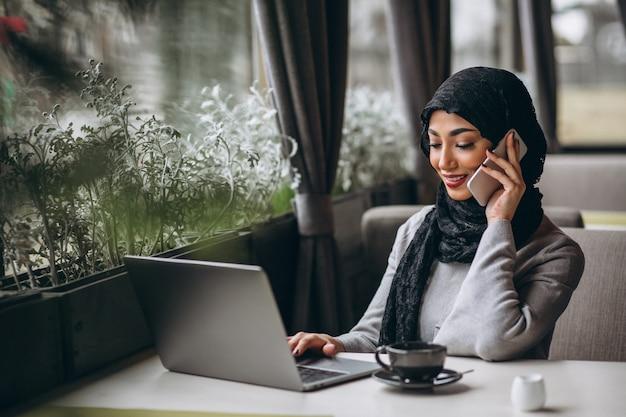 Mujer árabe en hijab dentro de un café trabajando en una computadora portátil Foto gratis