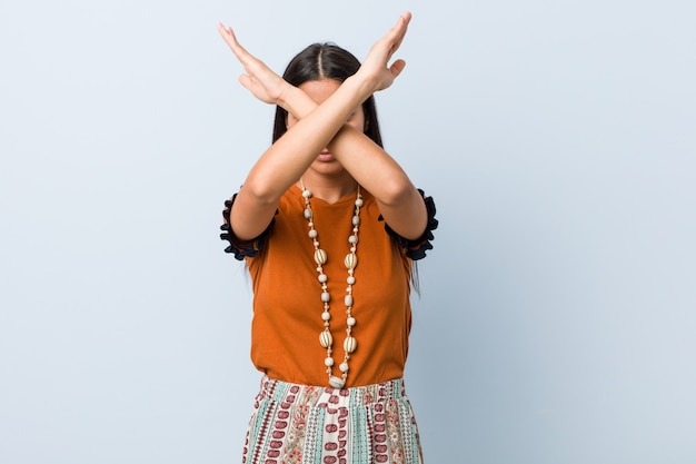 Mujer árabe joven que mantiene dos brazos cruzados, negación. Foto Premium