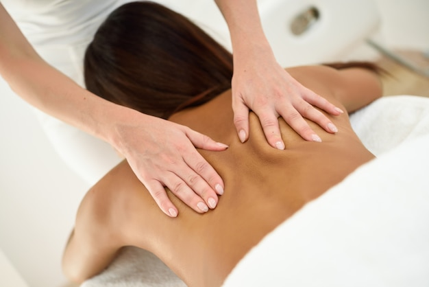 Mujer árabe que recibe un masaje en la espalda en un centro de spa. Foto gratis