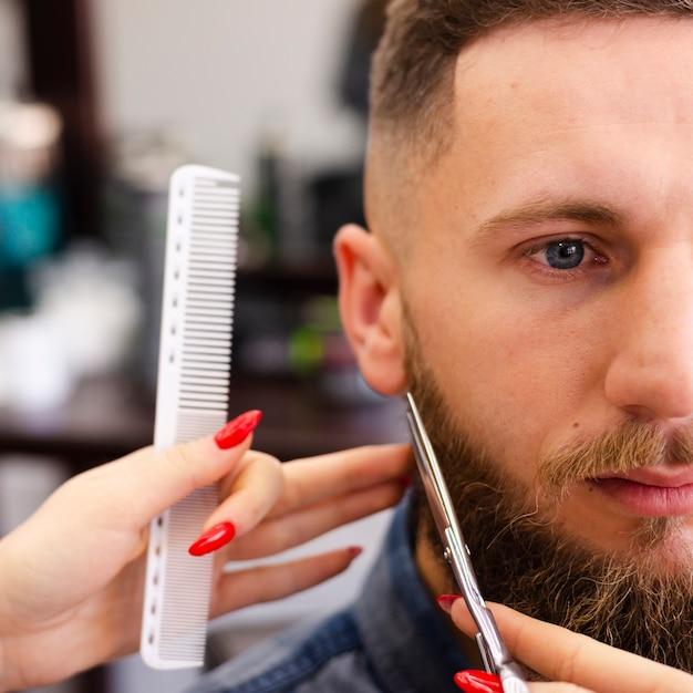 Mujer arreglando la barba de un cliente Foto gratis