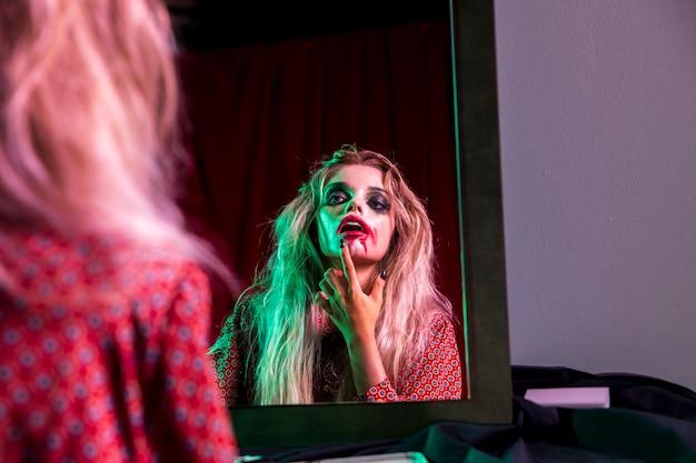Mujer arreglando su lápiz labial para la noche de halloween Foto gratis