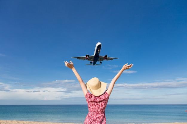 Mujer de asia que viaja, relaja vacaciones y mira el avión volando sobre el mar Foto Premium