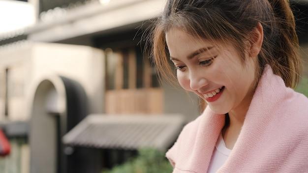 Mujer asiática alegre del blogger del backpacker que usa el smartphone para la dirección y que mira en mapa de ubicación mientras que viaja en chinatown en pekín, china. Foto gratis