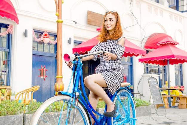 Mujer asiática alegre ciclismo Foto Premium