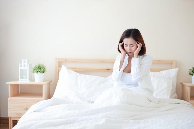 La mujer asiática atractiva y atractiva joven que llevaba la camisa blanca consiguió dolor de cabeza en cama en el dormitorio blanco con la cara infeliz. Foto Premium