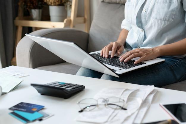Mujer asiática bastante joven que trabaja con la computadora portátil de la computadora para hacer los gastos caseros y los impuestos en sala de estar en casa. Foto Premium