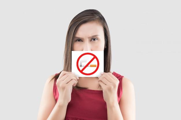 La mujer asiática en blusa roja está llevando a cabo la muestra de no fumadores en el libro blanco Foto Premium