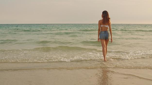 Mujer asiática caminando en la playa de arena. Foto gratis