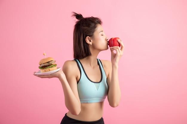Mujer asiática eligiendo entre hamburguesa y manzana roja en rosa Foto gratis