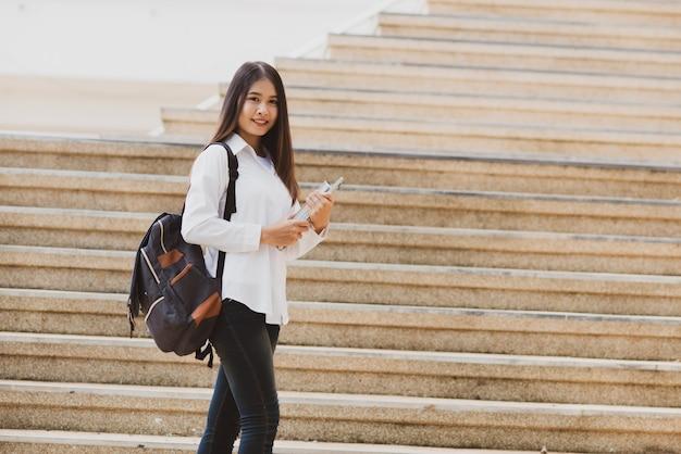 Mujer asiática del estudiante con el ordenador portátil y el bolso, concepto de la educación Foto gratis