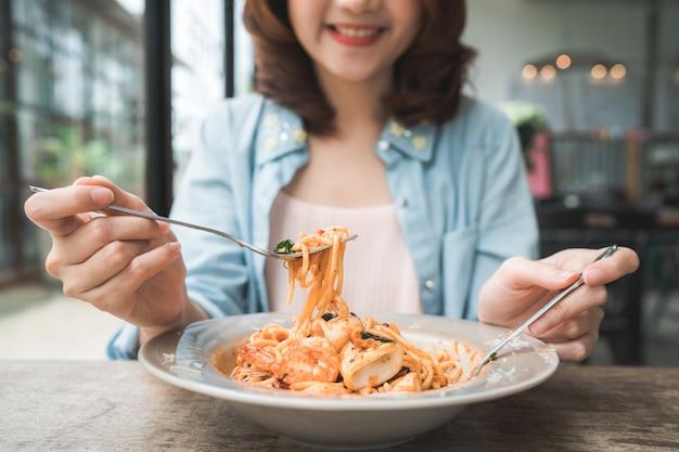 Mujer asiática feliz hermosa que come un plato de espagueti italiano de los mariscos en el restaurante o el café mientras que Foto gratis